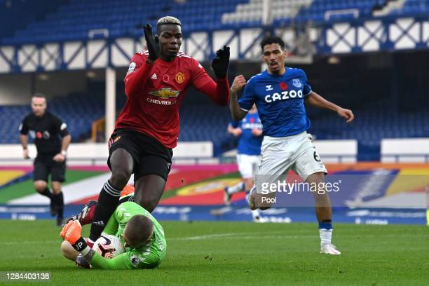 Jordan Pickford of Everton collects the ball from the feet of Paul Pogba of Manchester United during the Premier League match between Everton and...