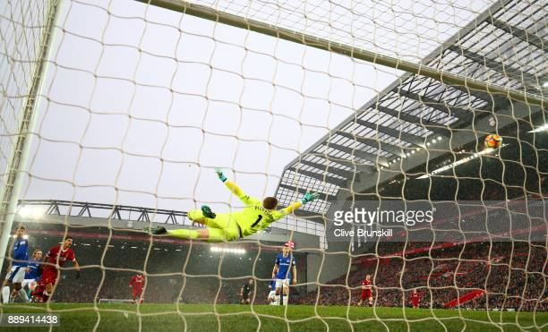 Jordan Pickford of Everton dives as Mohamed Salah of Liverpool scores his side's first goal during the Premier League match between Liverpool and...