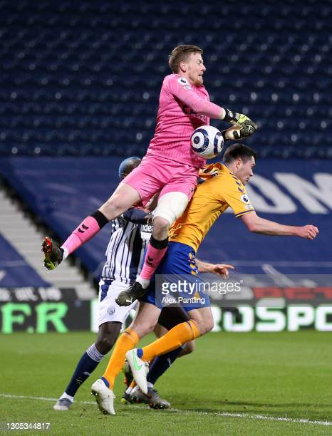 Jordan Pickford of Everton fails to catch the ball as he collides with team mate Michael Keane during the Premier League match between West Bromwich...