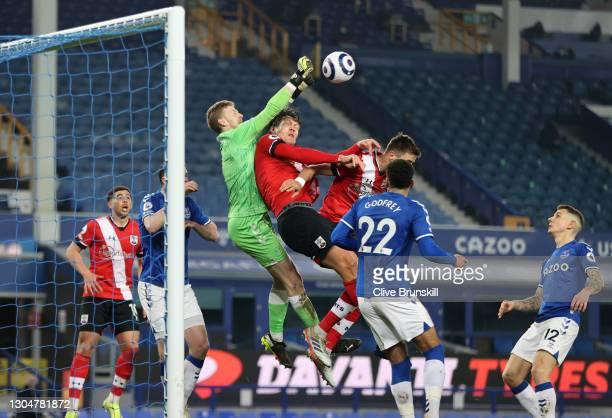 Jordan Pickford of Everton punches the ball away from Jannik Vestergaard and Jan Bednarek of Southampton during the Premier League match between...