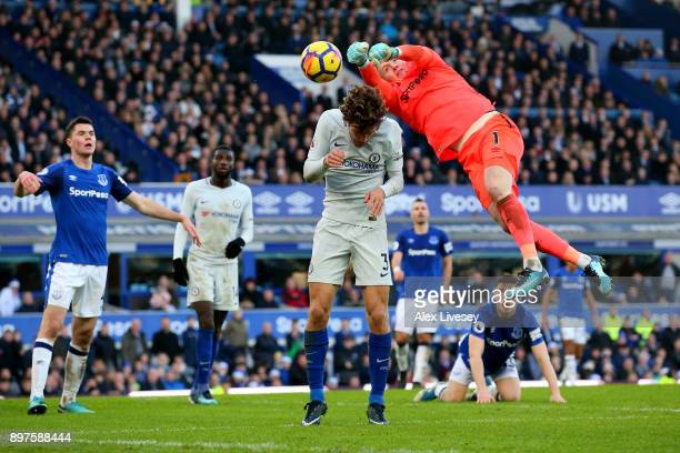 Jordan Pickford of Everton punches the ball away from Marcos Alonso of Chelsea during the Premier League match between Everton and Chelsea at...