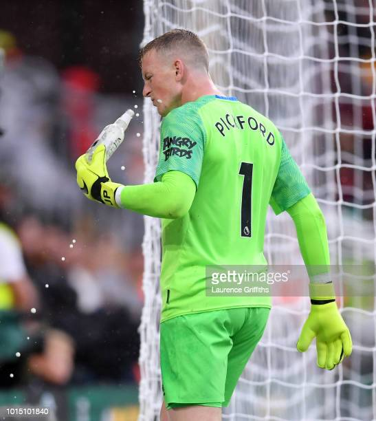 Jordan Pickford of Everton removes a bottle from the pitch after it was thrown at him during the Premier League match between Wolverhampton Wanderers...