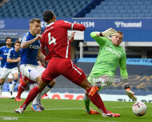 Jordan Pickford of Everton takes out Virgil van Dijk of Liverpool during the Premier League match between Everton and Liverpool at Goodison Park on...