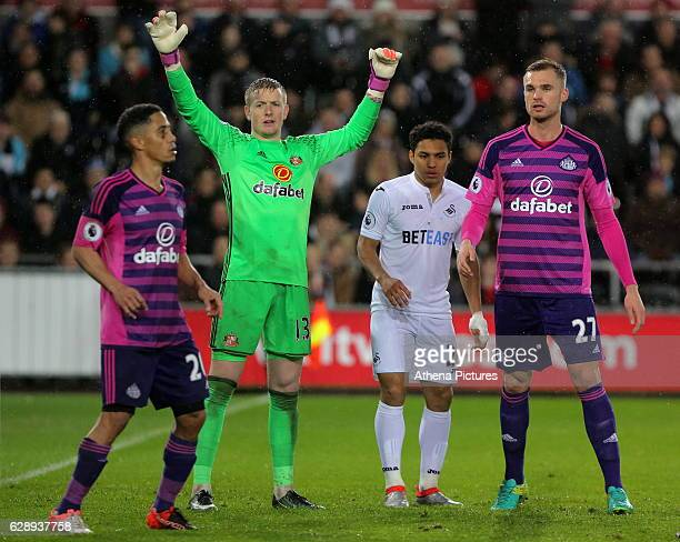 Jordan Pickford of Sunderland and Jefferson Montero of Swansea City wait for a cross during the Premier League match between Swansea City and...
