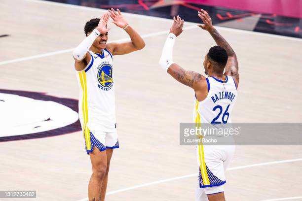 Jordan Poole and Kent Bazemore of the Golden State Warriors celebrate after a basket during the fourth quarter of a game against the Cleveland...