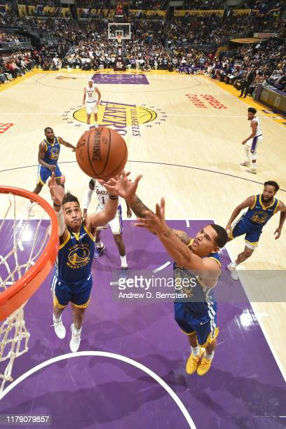 Jordan Poole and Kevon Looney of the Golden State Warriors go up for the rebound during a preseason game against the Los Angeles Lakers on October 16...