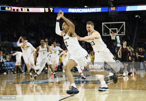 Jordan Poole and Moritz Wagner of the Michigan Wolverines celebrate Poole's 3-point buzzer beater for a 64-63 win over the Houston Cougars during the...