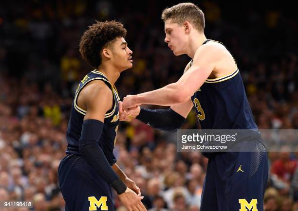 Jordan Poole and Moritz Wagner of the Michigan Wolverines react to a play during the first half of the 2018 NCAA Men's Final Four National...