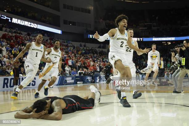 Jordan Poole and teammates of the Michigan Wolverines celebrate Poole's 3point buzzer beater for a 6463 win as Devin Davis of the Houston Cougars is...