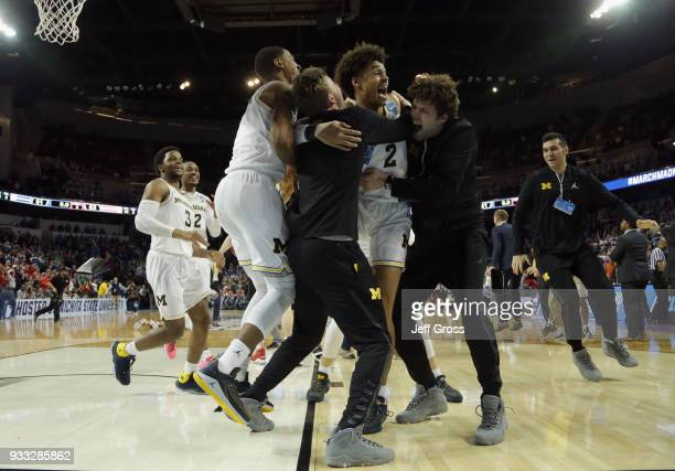 Jordan Poole and teammates of the Michigan Wolverines celebrate Poole's 3point buzzer beater for a 6463 win over the Houston Cougars during the...