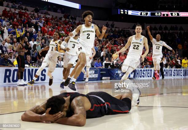 Jordan Poole and teammates of the Michigan Wolverines celebrate Poole's 3-point buzzer beater for a 64-63 win as Devin Davis of the Houston Cougars...