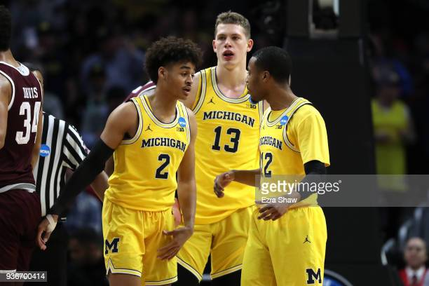 Jordan Poole Moritz Wagner and MuhammadAli AbdurRahkman of the Michigan Wolverines discuss the play against the Texas AM Aggies during the first half...