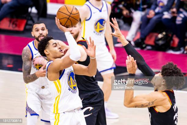 Jordan Poole of the Golden State Warriors shoots the ball over Brodric Thomas of the Cleveland Cavaliers during the fourth quarter at Rocket Mortgage...