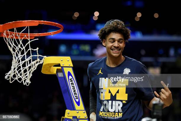 Jordan Poole of the Michigan Wolverines cuts down the net after the Wolverines 5854 victory against the Florida State Seminoles in the 2018 NCAA...