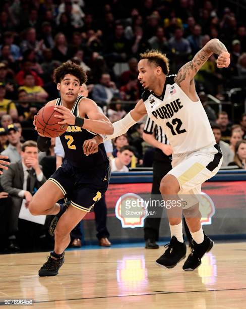 Jordan Poole of the Michigan Wolverines drives against Vincent Edwards of the Purdue Boilermakers during the championship game of the Big Ten...
