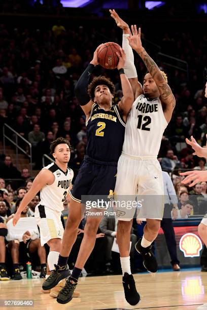 Jordan Poole of the Michigan Wolverines goes up for a shot against Vincent Edwards of the Purdue Boilermakers during the championship game of the Big...