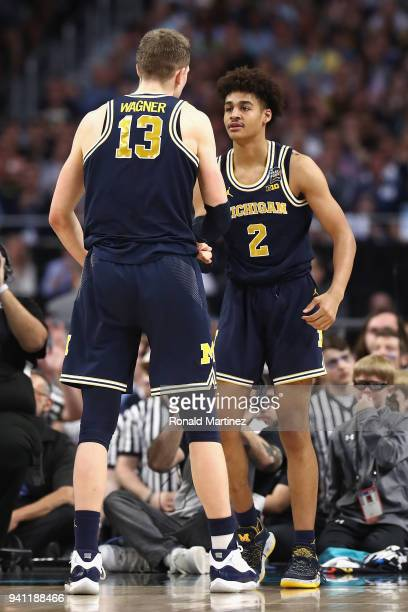 Jordan Poole of the Michigan Wolverines reacts with Moritz Wagner in the first half against the Villanova Wildcats during the 2018 NCAA Men's Final...