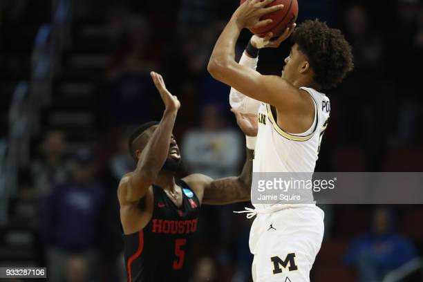 Jordan Poole of the Michigan Wolverines shoots a 3point buzzer beater against Corey Davis Jr #5 of the Houston Cougars in the second half during the...