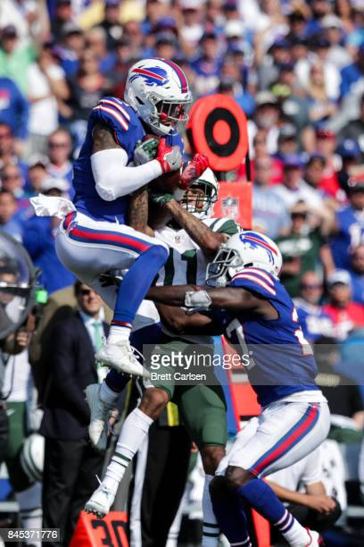 Jordan Poyer of the Buffalo Bills and Robby Anderson of the New York Jets and Tre'Davious White of the Buffalo Bills go for the ball during the...