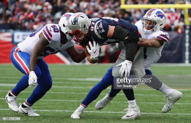 Jordan Poyer of the Buffalo Bills tackles Rob Gronkowski of the New England Patriots during the game at Gillette Stadium on December 24 2017 in...