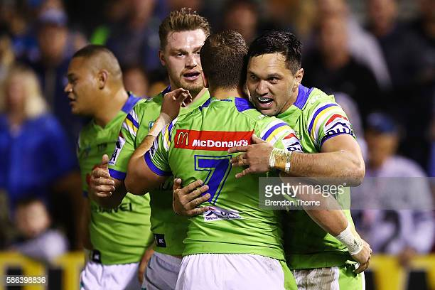 Jordan Rapana of the Raiders celebrates with team mates after scoring his second try during the round 22 NRL match between the Cronulla Sharks and...