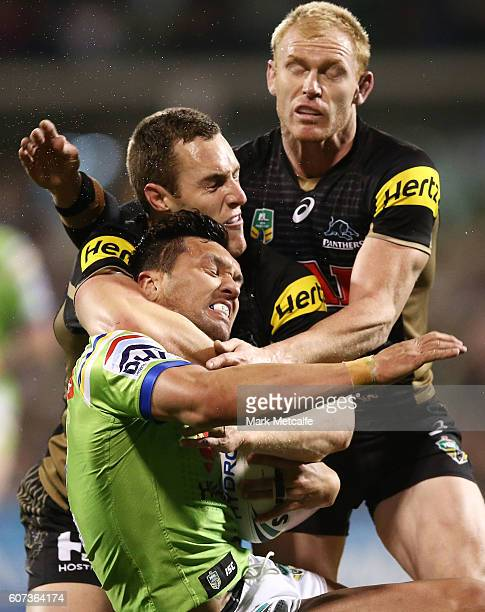 Jordan Rapana of the Raiders is tackled by Isaah Yeo and Peter Wallace of the Panthers during the second NRL Semi Final match between the Canberra...