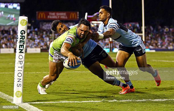 Jordan Rapana of the Raiders scores a try in the tackle of Sosaia Feki and Ricky Leutele of the Sharks during the round one NRL match between the...