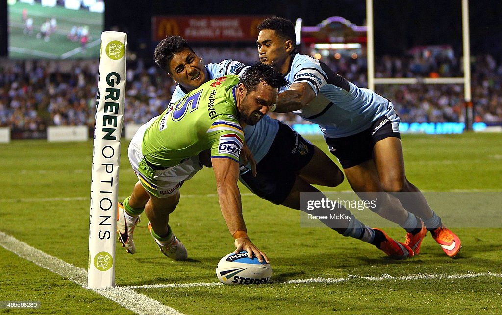Jordan Rapana of the Raiders scores a try in the tackle of Sosaia Feki and Ricky Leutele of the Sharks during the round one NRL match between the Cronulla Sharks and the Canberra Raiders at Remondis Stadium on March 8, 2015 in Sydney, Australia.