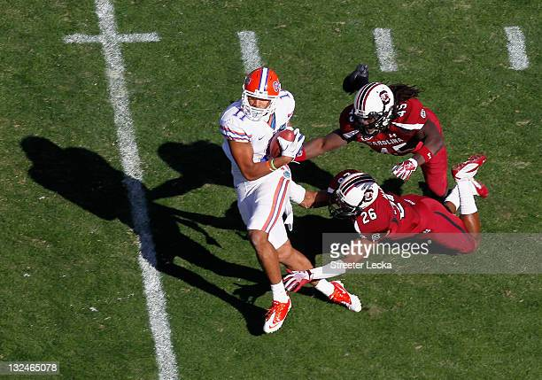Jordan Reed of the Florida Gators gets away from teammates Rodney Paulk of the South Carolina Gamecocks and Antonio Allen during their game at...