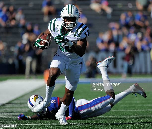 Jordan Reid of the Ohio Bobcats gets past cornerback Brandon Stewart of the Kansas Jayhawks as he looks to pick up extra yards in the third quarter...