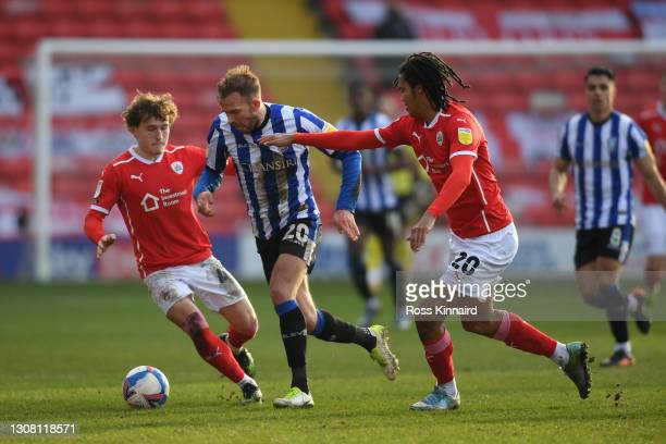 Jordan Rhodes of Sheffield Wednesday is put under pressure by Callum Styles and Toby Sibbick of Barnsley FC during the Sky Bet Championship match...