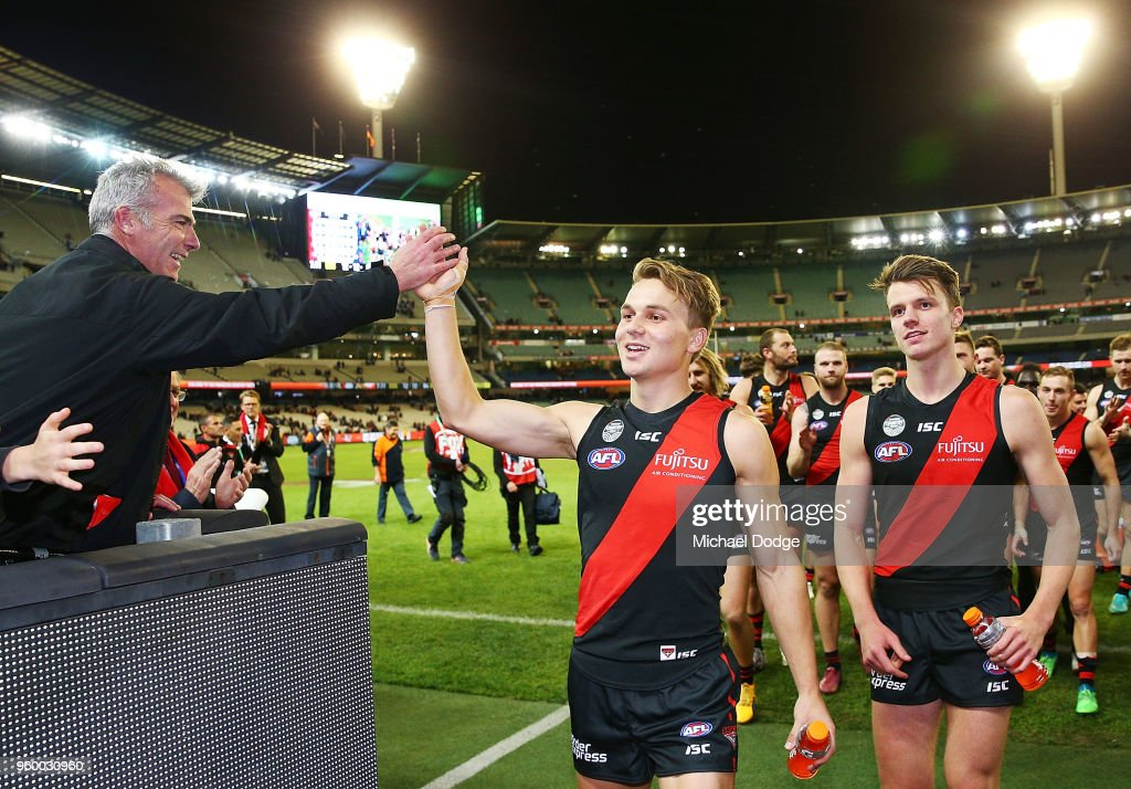 Jordan Ridley of Essendon (R) and Dylan Clarke celebrate their first win during the round nine AFL match between the Essendon Bombers and the Geelong Cats at Melbourne Cricket Ground on May 19, 2018 in Melbourne, Australia.