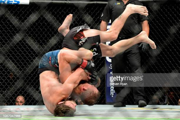 Jordan Rinaldi of the United States takes down Jason Knight of the United States in their featherweight bout during the UFC 230 event at Madison...