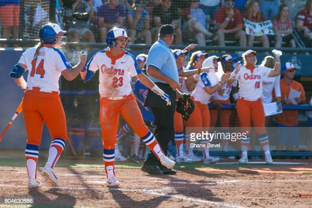 Jordan Roberts and Nicole DeWitt of the University of Florida celebrate after DeWitt slides into home plate during the Division I Women's Softball...