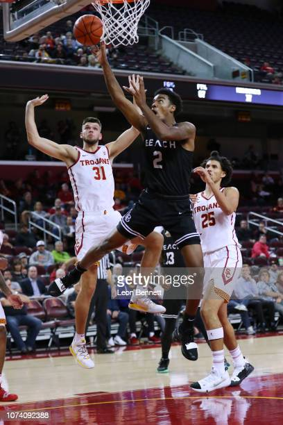Jordan Roberts of the Long Beach State 49ers goes to the basket against Nick Rakocevic and Bennie Boatwright of the USC Trojans during a college...