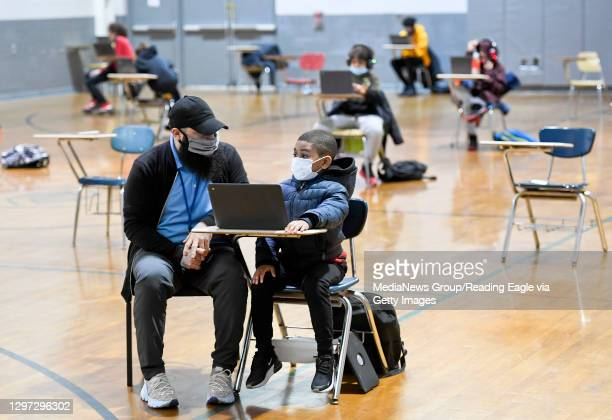 Jordan Rodriguez, director of the Mulberry Street club, works with Santana Sanford a second grade student, as he does his school work on a laptop...