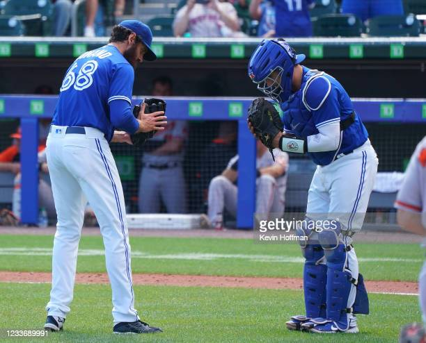 Jordan Romano of the Toronto Blue Jays and Reese McGuire bow to each other after beating the Baltimore Orioles at Sahlen Field on June 27, 2021 in...