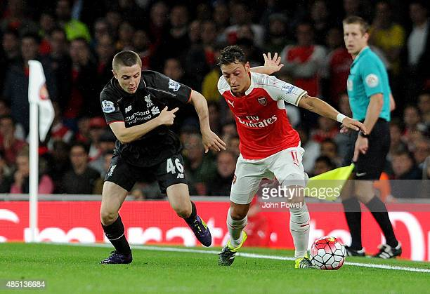 Jordan Rossiter of Liverpool competes with Mesut Ozil of Arsenal during the Barclays Premier League match between Arsenal and Liverpool on August 24...