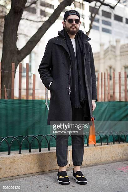 Jordan Santschi is seen on Michigan Avenue wearing a black wool John Varvatos coat black Rag Bone scarf white Gap shirt dark grey Uniqlo pants...