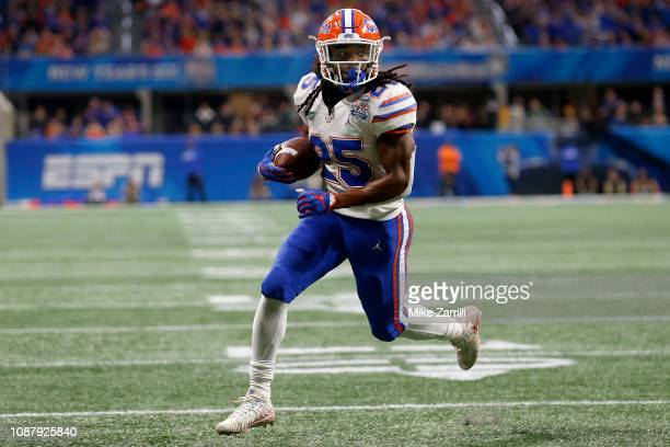 Jordan Scarlett of the Florida Gators scores a third quarter rushing touchdown against the Michigan Wolverines during the ChickfilA Peach Bowl at...