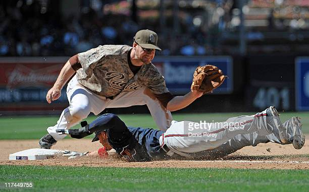 Jordan Schafer of the Atlanta Braves gets back to third base under the tag of Chase Headley of the San Diego Padres after leading off during the...