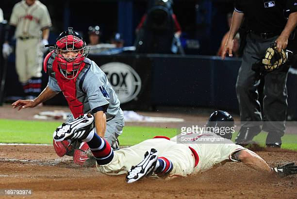 Jordan Schafer of the Atlanta Braves scores the gamewinning run in the 10th inning against Kurt Suzuki of the Washington Nationals at Turner Field on...