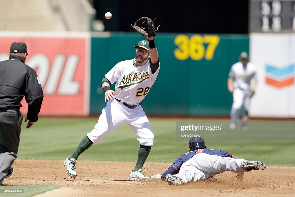 Jordan Schafer #1 of the Minnesota Twins slides safely under the tag of Eric Sogard #28 of the Oakland Athletics to steal second base in the third inning at O.co Coliseum on August 10, 2014 in Oakland, California.