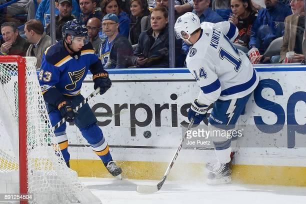 Jordan Schmaltz of the St Louis Blues and Chris Kunitz of the Tampa Bay Lightning look for control of the puck at Scottrade Center on December 12...