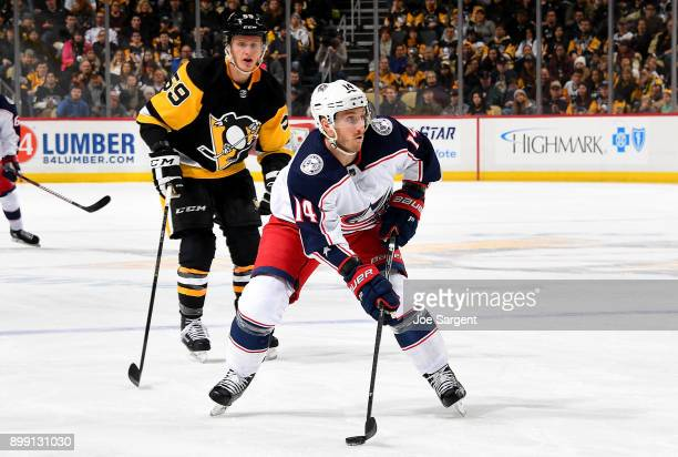 Jordan Schroeder of the Columbus Blue Jackets handles the puck against Jake Guentzel of the Pittsburgh Penguins at PPG Paints Arena on December 27...