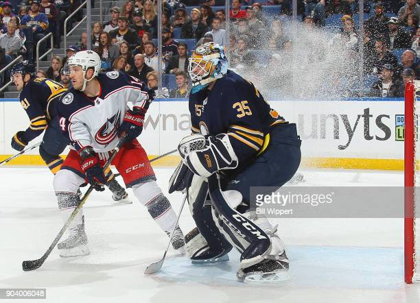 Jordan Schroeder of the Columbus Blue Jackets leaves a wake of ice spray as he stops in front of Linus Ullmark of the Buffalo Sabres during the...