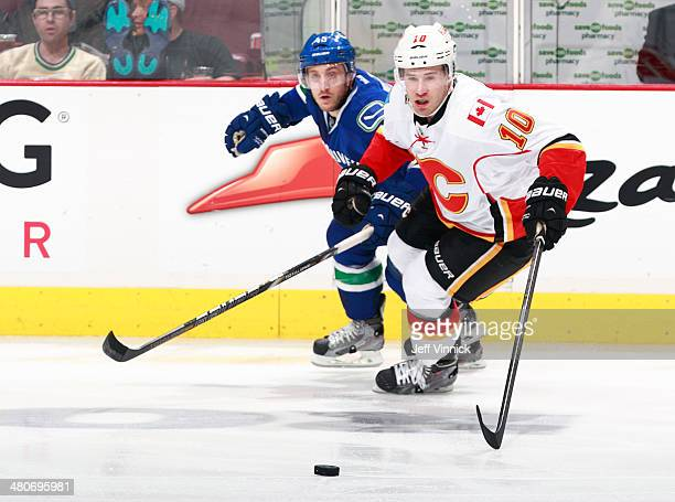 Jordan Schroeder of the Vancouver Canucks and Corban Knight of the Calgary Flames skate up ice during their NHL game at Rogers Arena March 8 2014 in...
