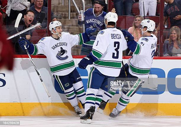 Jordan Schroeder of the Vancouver Canucks celebrates with Kevin Bieksa and Mason Raymond after Schroeder scored a third period goal against the...