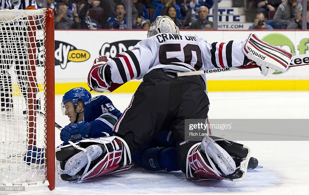 Jordan Schroeder #45 of the Vancouver Canucks crashes into goalie Corey Crawford #50 of the Chicago Blackhawks during the third period in NHL action on February 01, 2013 at Rogers Arena in Vancouver, British Columbia, Canada.