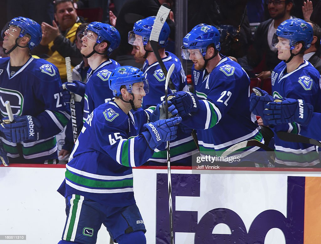 Jordan Schroeder #45 of the Vancouver Canucks is congratulated at the bench after scoring in the shootout against the Chicago Blackhawks during their NHL game at Rogers Arena February 1, 2013 in Vancouver, British Columbia, Canada. Vancouver won 2-1 in a shootout.